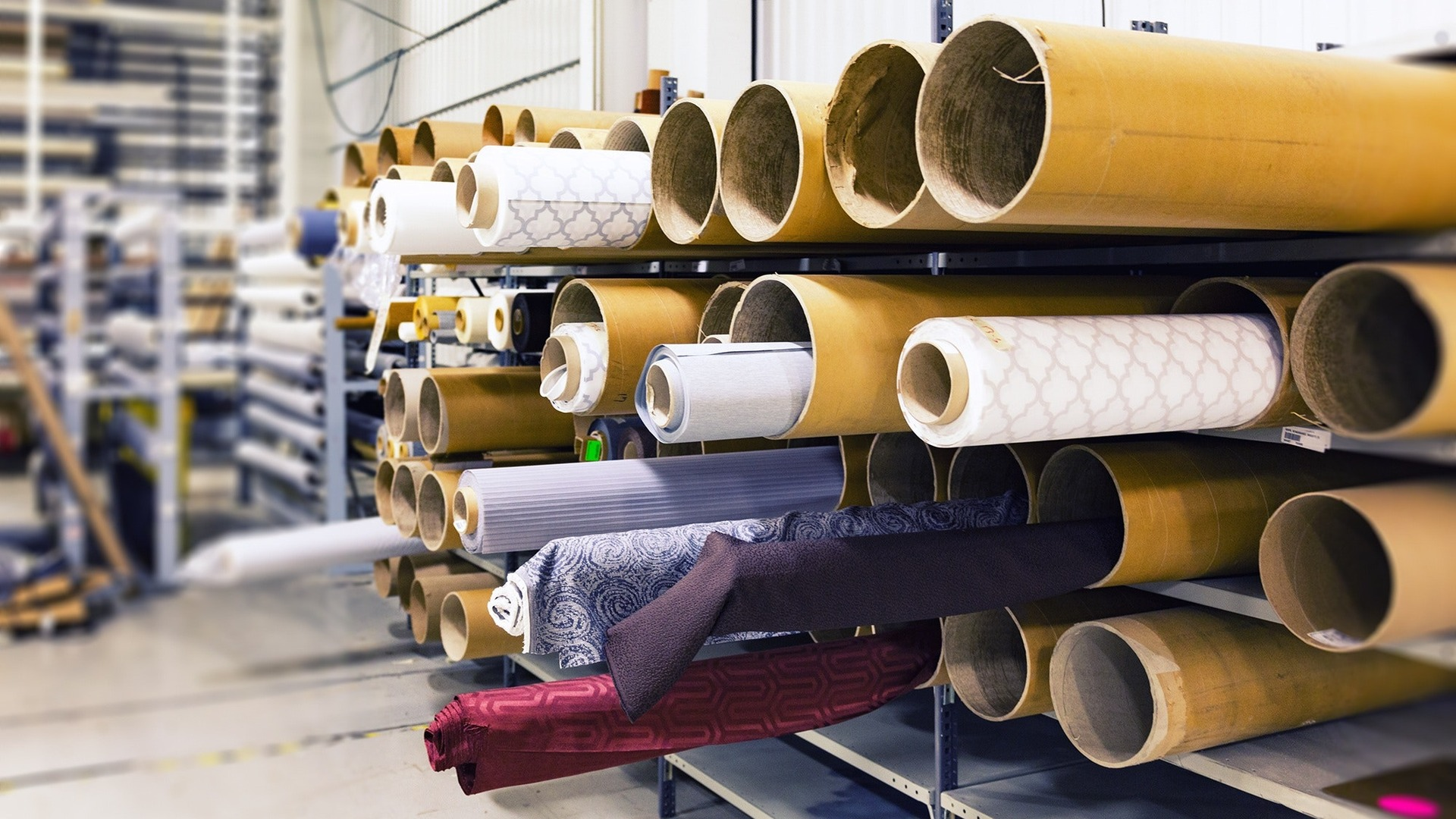 Multiple rolls of fabric in a bright room