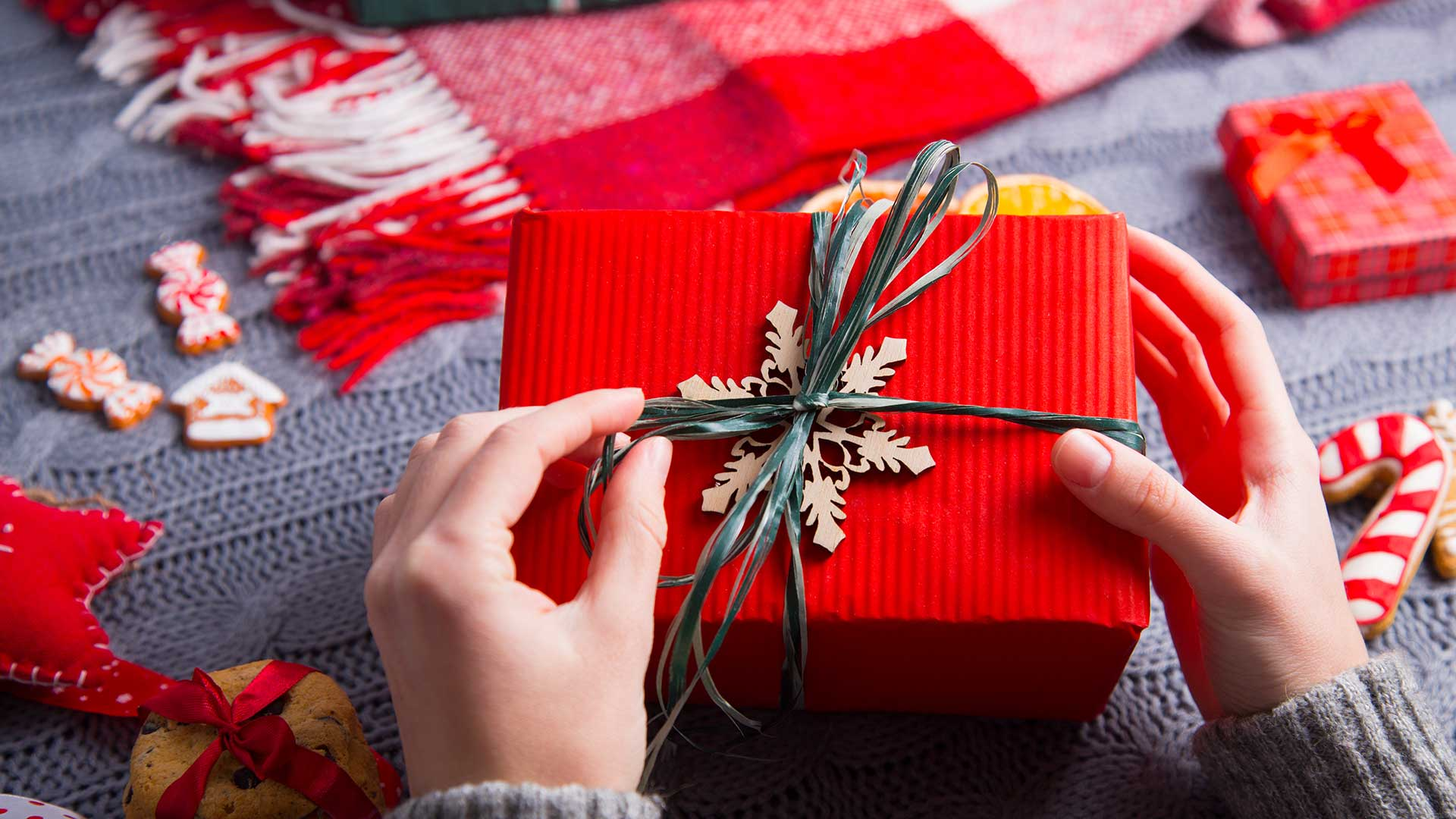 A woman wearing a grey jumper wraps a Christmas gift in red paper with a ribbon and cardboard snowflake for trim.