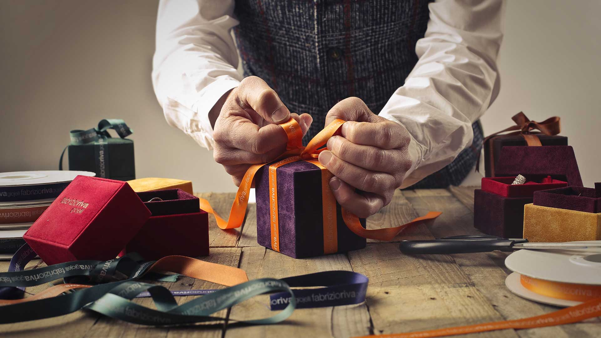 A man wearind a knitted vest and white shirt with long sleeves wraps a small parcel with purple paper and orange ribbon.