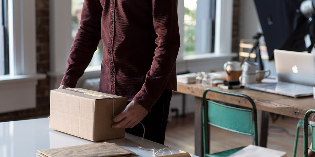 A man in a red, button-up shirt wraps twine around a brown, cardboard box.
