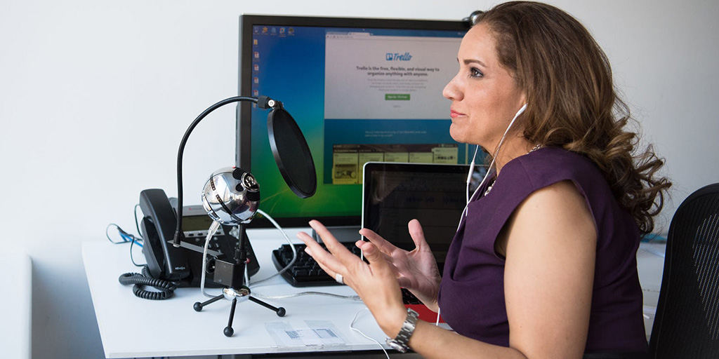 A woman with dark hair and a purple dress sits in front of her desk recording a podcast